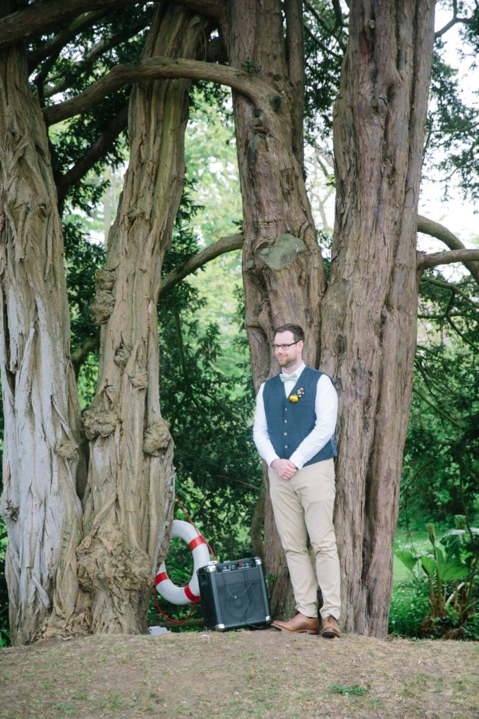 groomsmen standing under a tree