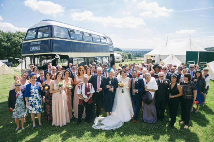 Group wedding photograph in front of vintage bus